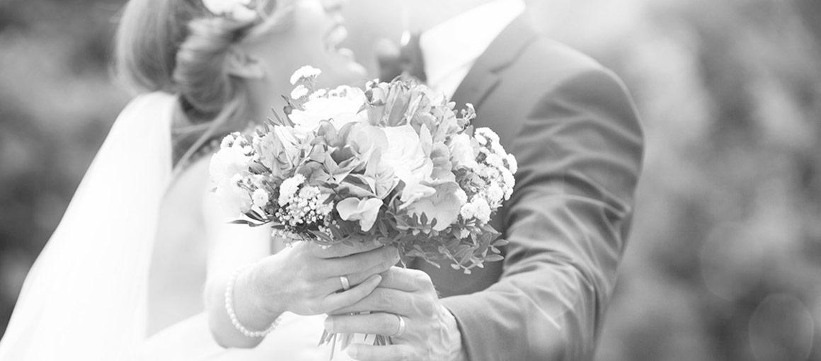 Hochzeitsplanung – Brautpaar mit Brautstrauss